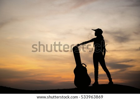 Silhouette Girl with guitar on sunset.