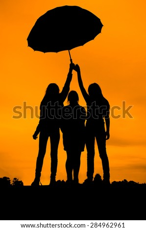 Silhouette girls against the evening sky .  Under the umbrella.