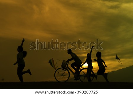 Silhouette, group of happy children playing on meadow, sunset