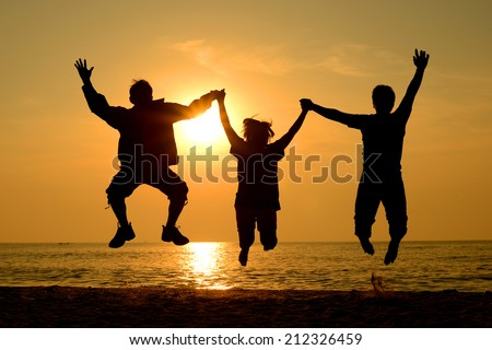 Silhouette Group of happy people man and woman jumping on the beach