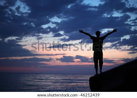 Silhouette guy placed hands in sides on breakwater in evening near sea