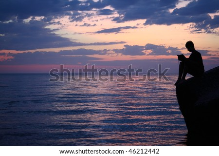 Silhouette guy sitting on breakwater in evening near sea, reads book, wide angle - stock photo