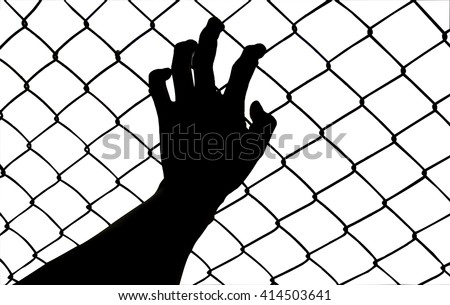 silhouette hand holding on chain link fence - stock photo