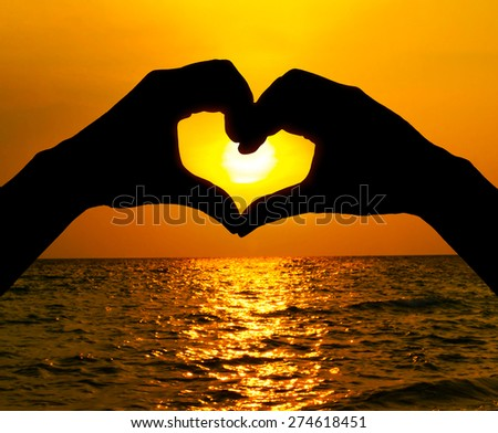 Silhouette hand in heart shape and sunrise over the ocean  - stock photo