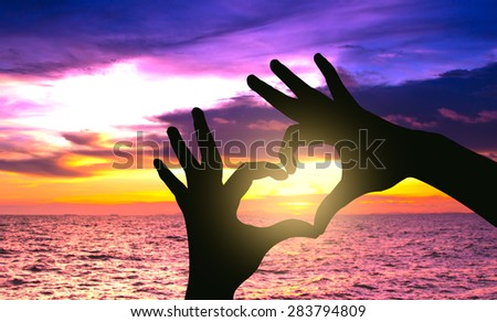 Silhouette hand in heart shape on sunset over the sea - stock photo