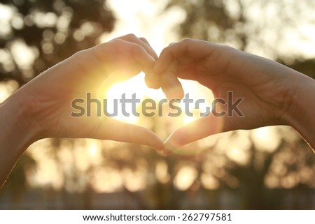 silhouette hand in heart shape with sunlight and flare  - stock photo