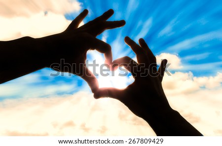 Silhouette hands in heart shape and blue sky - stock photo