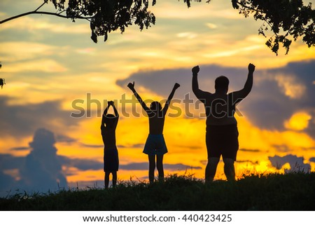 Silhouette happy kids under a large tree. Successful