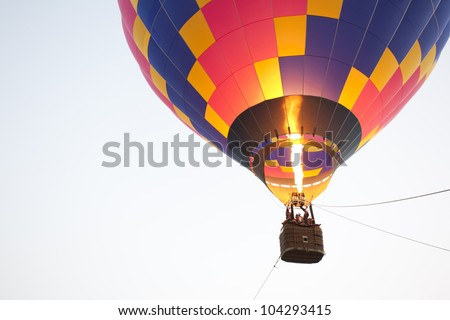 Silhouette hot air balloon landing with many people - stock photo