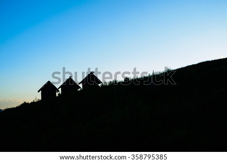 silhouette house and hill on blue sky background - stock photo