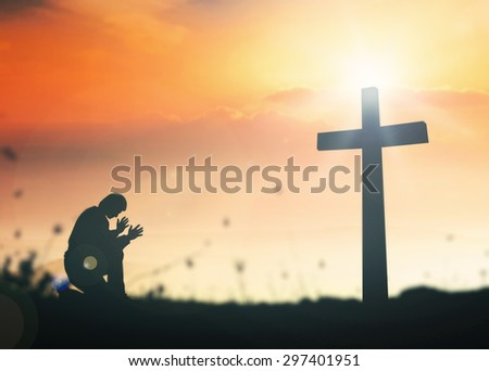 Silhouette human kneeling and praying over the cross on beautiful sunset with amazing light background. - stock photo