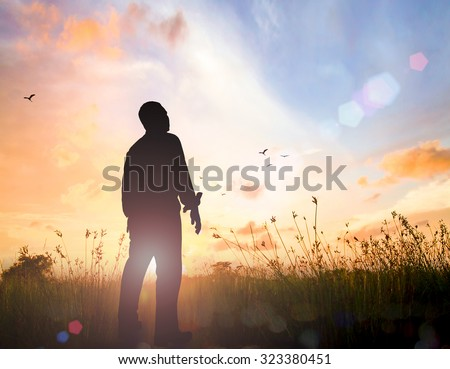 Silhouette human standing over beautiful golden autumn sunset background. World Mental Health Day, Thanksgiving, Christmas, Forgiveness, Mercy, Repentance, Reconcile, Glorify,  Evangelical concept. - stock photo