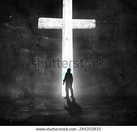 Silhouette human standing over the white cross in dark room and looking the beach. - stock photo