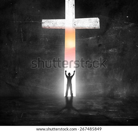 Silhouette human standing over the white cross in dark room and looking the beautiful sunset. - stock photo