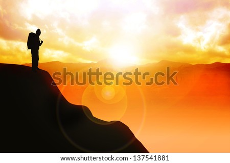 Silhouette illustration of a man with backpack on top of  the mountain - stock photo
