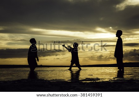 silhouette image concept of young boys playing at the beach with beautiful sunrise sunset background. sandy beaches and reflection on water