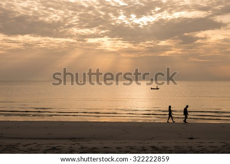 Silhouette image of couple walking along the beach with sun ray or beam with soft focused for nature background  - stock photo
