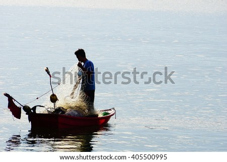 Silhouette image of Fisherman on boat with blue water background at Songkhla Lake Thailand:Select focus with shallow depth of field:ideal use for background. - stock photo