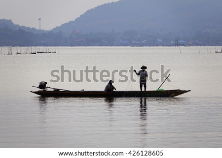 Silhouette image of fisherman working on boat in lake on morning time:select focus with shallow depth of field.