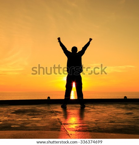 Silhouette Image of Happy Man Showing Winner Action - stock photo