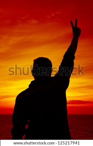Silhouette Image of Man Raising His Hand Showing Two Fingers - stock photo