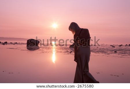 silhouette image of pink sunset and sad lady - stock photo