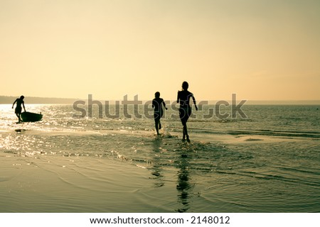 silhouette image of two running girls and muscular man in water