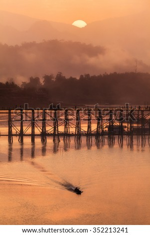 Silhouette image of wooden bridge and sailing boat during sunrise at Sangkhlaburi, Thailand.