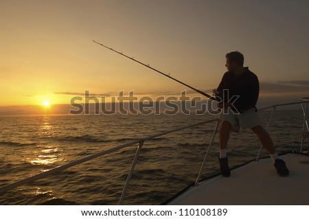 Silhouette image of young man fishing on yacht - stock photo
