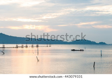 Silhouette image the lake and ,water,boat,fisherman at Songkhla Thailand during sunset.Motion blur, soft focus due to slow shutter speed.