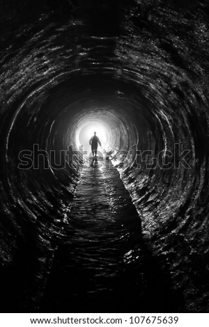 silhouette in a  communication tunnel. Light at End of Tunnel - stock photo
