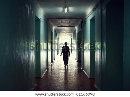 silhouette in a corridor. Light at the end of the tunnel concept - stock photo