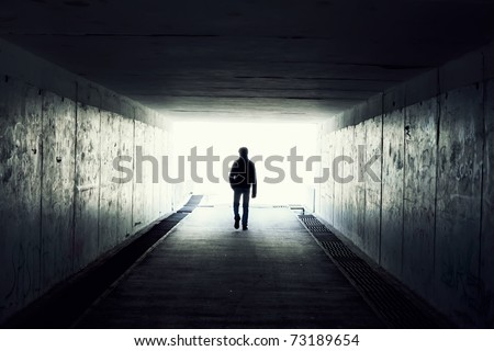 silhouette in a subway tunnel. Light at End of Tunnel - stock photo