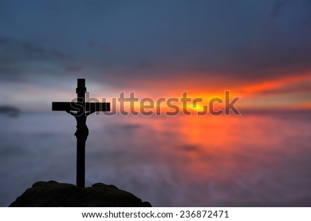 Silhouette Jesus and the cross over blurred sunset  - stock photo