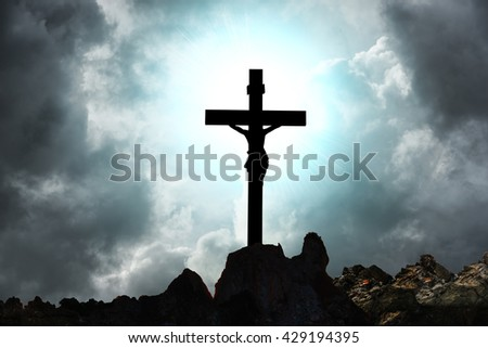 Silhouette Jesus and the cross over storm on mountain top - stock photo