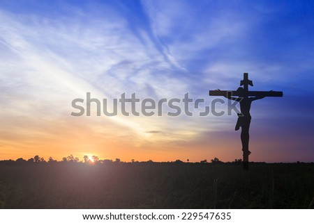 Silhouette Jesus and the cross over sunset background - stock photo