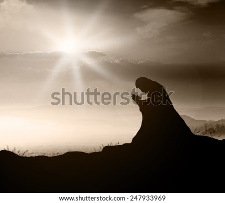 Silhouette Jesus Christ of Nazareth or believer kneeling and praying over beautiful sunrise or sunset background. Sepia tone. - stock photo