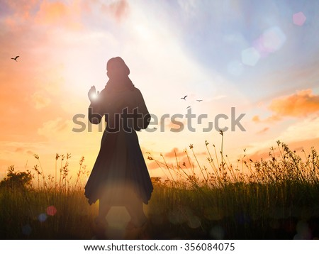 Silhouette Jesus Christ on sunrise with amazing light background. Thankful Adoration Glorify Peace Evangelical Hallelujah Blessing Religion Hosanna Divine Mercy Sacred Heart He is Risen concept. - stock photo