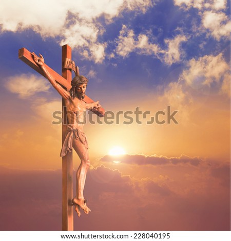 Silhouette Jesus Christ on the cross at the mountain golgotha representing the day of christ crucifixion in a sunset background. - stock photo