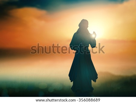 Silhouette Jesus on blur beautiful autumn sunset with amazing light background. He Is Risen Thankful Adoration Glorify Peace Evangelical Hallelujah Blessing Amen Hope Religion Hosanna Morning concept - stock photo