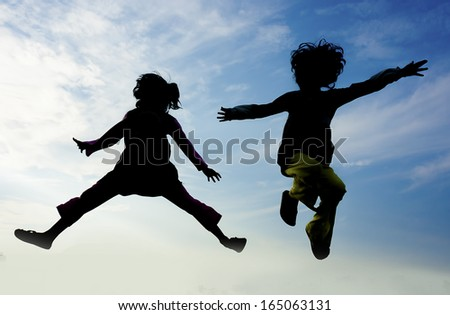 Silhouette kids jumping with nice blue sky background - stock photo
