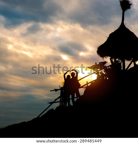 Silhouette love couple make heart shape with sunset.  - stock photo