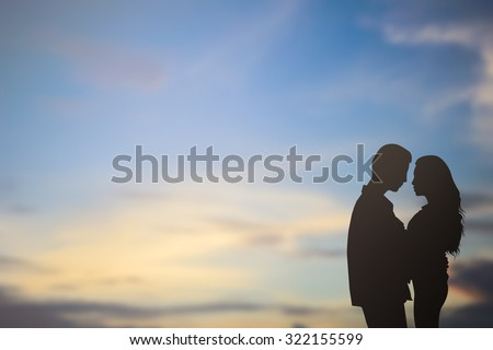 silhouette lover couple over sunset backgrounds at the beach :black shadow loving people hug and try to kiss for show about their love each other : passion in love concept.decorate,design,valentines - stock photo