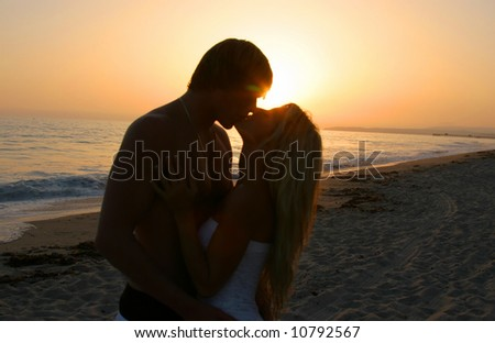 Silhouette Lovers Kissing on tne Beach at Sunset - stock photo
