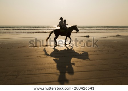 Silhouette man and horse on the beach  - stock photo