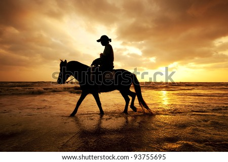 Silhouette man and horse on the beach with sunset sky environment at Thailand - stock photo