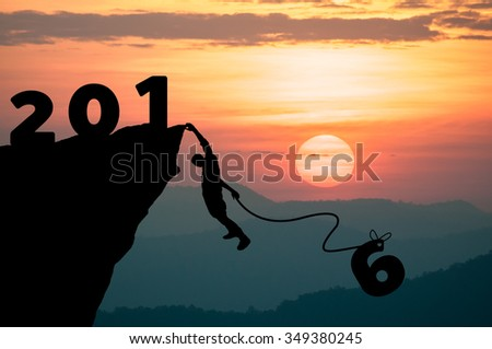 Silhouette Man climbs into cliff to make the word the New Year 2016. - stock photo