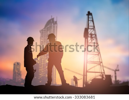 Silhouette man engineer looking construction worker in a building site over Blurred construction worker on construction site - stock photo