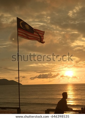 silhouette man enjoying sunset with a malaysian flag waiving