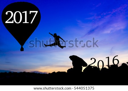 Silhouette man jumping between 2016 and 2017 hot air balloon wording.